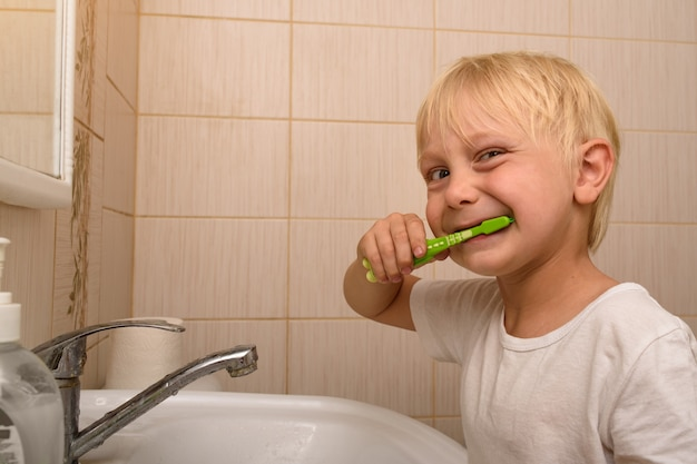 Blond boy diligently brushes his teeth in the bathroom. healthy habits