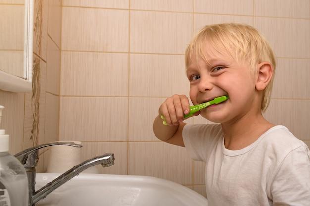 金髪の少年は、バスルームで熱心に歯を磨きます。健康的な習慣
