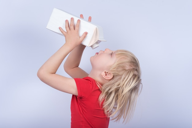 Blond boy drinking milk out of carton