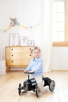 Blond boy drives a retro toy car in his children room. cute baby playing in kindergarten. childhood concept. child development concept. bright children's room in the scandinavian style. decor room