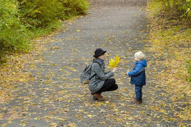 金髪の少年は彼の母親に黄色の葉の花束を与えます