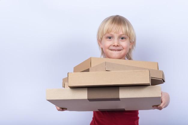 Белокурый мальчик держа коробки пиццы на белой предпосылке. доставка пиццы на дом концепции.