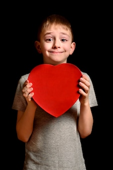 Blond boy holding a red box in the shape of a heart on black