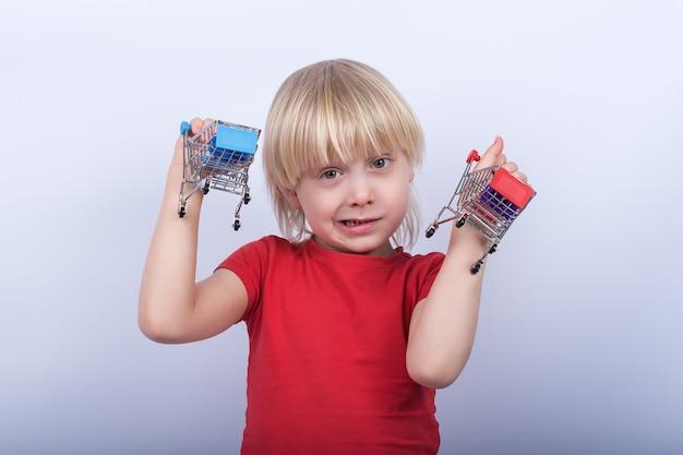 Белокурый мальчик держит магазинной тележкаи игрушки на белой предпосылке. магазин для ребенка