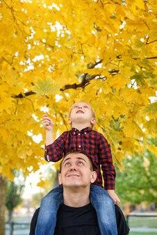 父親の肩に座っている格子縞のシャツを着た金髪の少年
