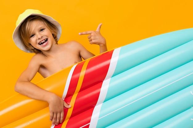 Белокурый мальчик в летней панаме с надувной плавательной доской на оранжевом