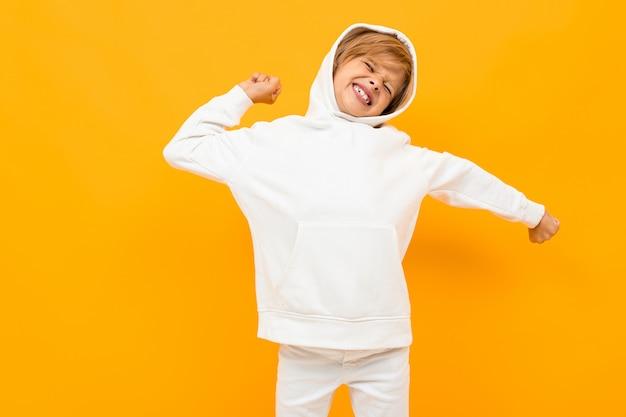 Белокурый мальчик в белой толстовке с громким криком на оранжевом