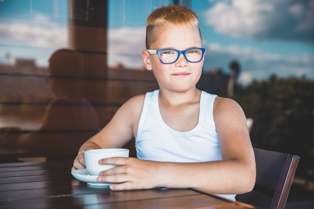コーヒーを飲むレストランで白いtシャツを着た金髪の少年