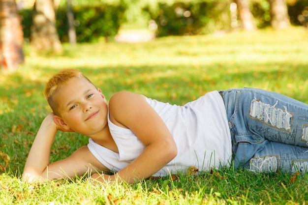 Блондинка в белой футболке лежит на траве в парке