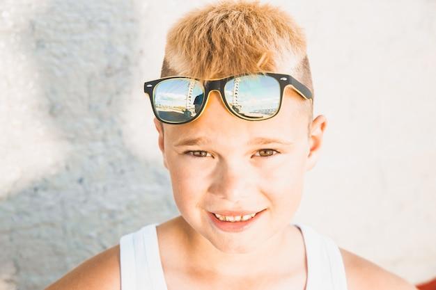Белокурый мальчик в белой футболке с очками на голове. портрет крупным планом