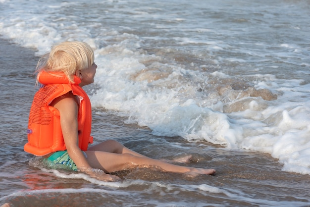 Блондинка мальчик в надувном жилете для плавания сидит на берегу моря в воде