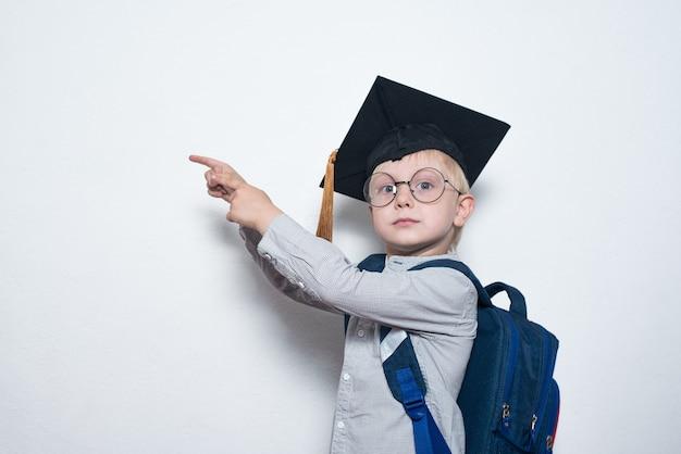 Белокурый мальчик в очках с серьезным взглядом показывает на борту. мальчик в студенческой шляпе. детские достижения. копировать пространство