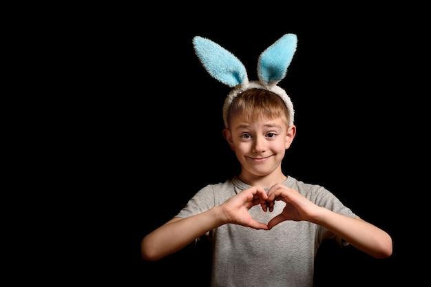 Белокурый мальчик в заячьих ушах сложил руки в форме сердца на груди на черной поверхности. концепция любви и семьи. скопируйте пространство.
