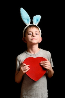 Блондинка в заячьих ушах держит красную коробку в форме сердца на черной стене