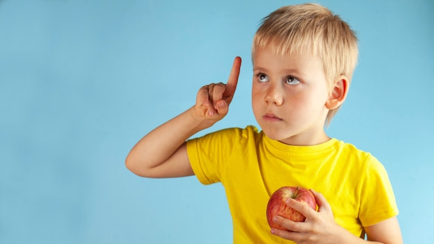 The blond boy is holding an apple in his hands and raising his finger up thoughtfully looks up. nutrition in children.