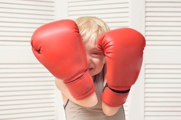 金髪の少年は2つのボクシンググローブで保護されています。ポートレート
