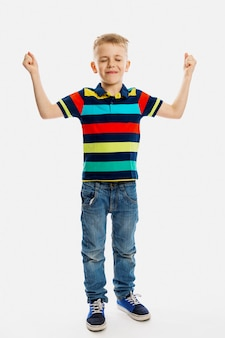 A blond boy in jeans and a multicolored t-shirt stands with his eyes closed and his hands up.