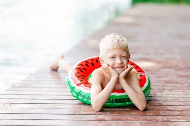 A blond boy lies on pier near a lake with a circle in the summer