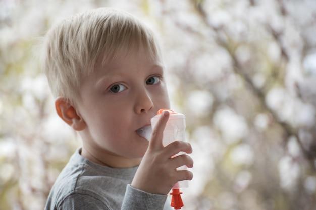 Белокурый мальчик делает ингаляции в домашних условиях. цветущие деревья на заднем плане. профилактика