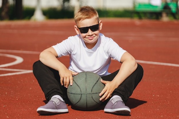 Blond boy sitting on basketball court with ball in summer. high quality photo
