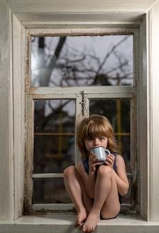 Белокурый мальчик сидит на старом шелушащемся деревянном подоконнике с металлической кружкой в руках
