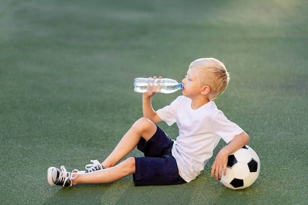 A blond boy in a sports uniform sits on a football field with a soccer ball and drinks water from a bottle
