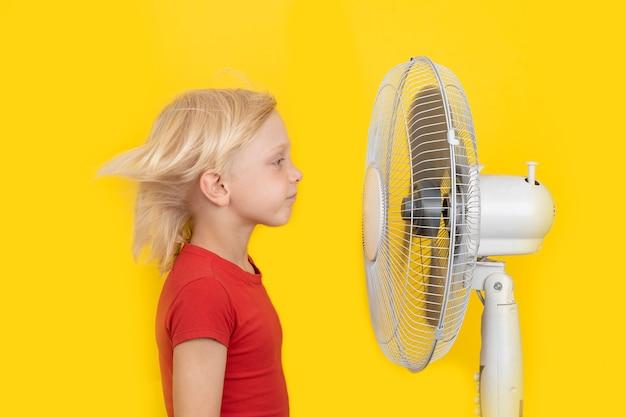 금발 소년은 밝은 노란색 배경에 인공호흡기 근처에 서 있습니다. 뜨거운 여름.