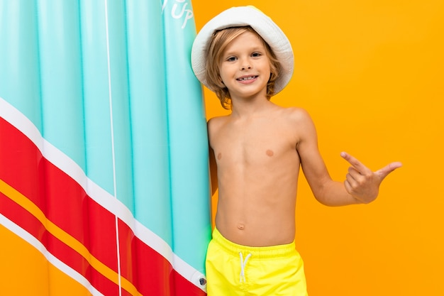 Blond boy in a summer panama with an inflatable swimming board on yellow