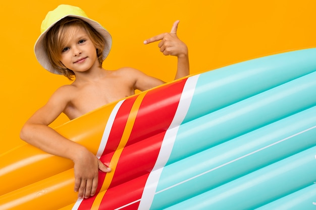 Blond boy in a summer panama with an inflatable swimming mattress on orange