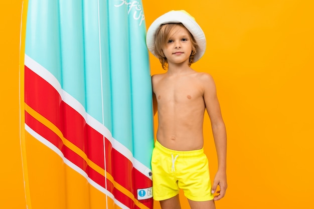 Blond boy in a summer panama and yellow swimming trunks with an inflatable swimming board on orange