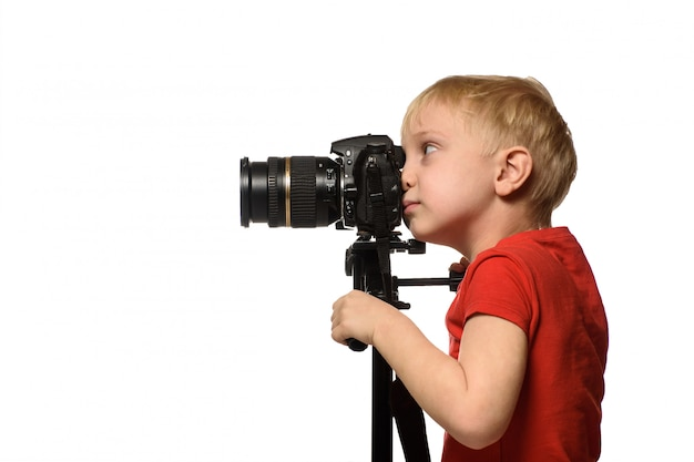 Blond boy takes pictures with a camera