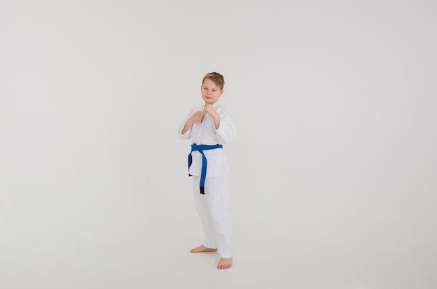 Blond boy in a white kimono with a blue belt stands in defense on a white wall
