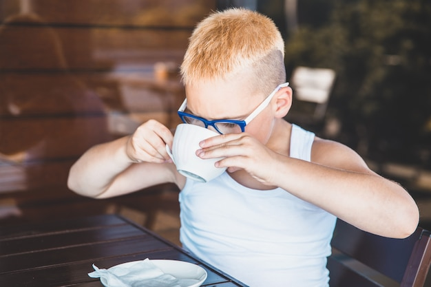 Blond boy in a white t-shirt in a restaurant drinking coffee