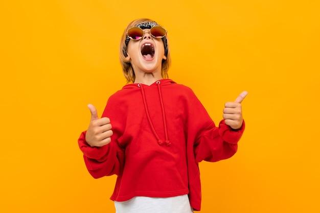 Белокурый мальчик с банданой на голове в красном свитере и очках показывает класс на оранжевом фоне.