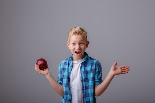 彼の手でリンゴを持つ金髪の少年