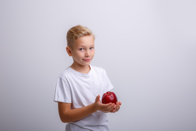Blond boy with an apple in his hands