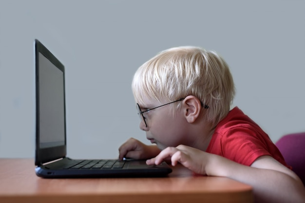 Blond boy with glasses sits his nose buried in a laptop. internet and preschooler