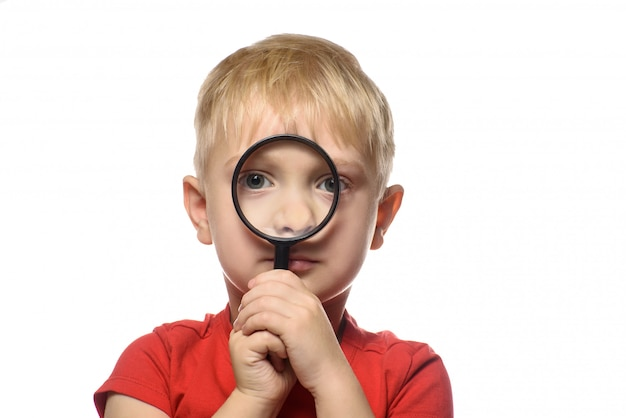 Blond boy with a magnifying glass in his hands. little explorer.