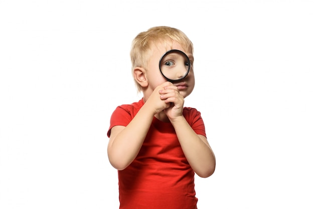 Blond boy with a magnifying glass in his hands