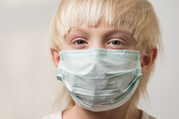 細菌を防ぐマスクを持つ金髪の少年。インフルエンザウイルスの保護。 covid 19