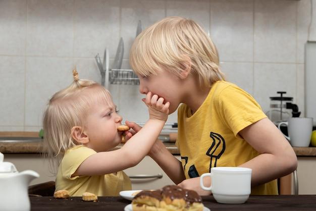 금발의 형제와 자매는 서로 쿠키를 먹입니다. 형제 자매. 어린이 및 유해한 과자
