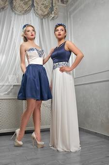 青と白のドレスでポーズをとったブロンド、ブルネットの女性