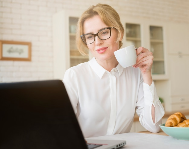 Blond business woman drinking coffee while using laptop