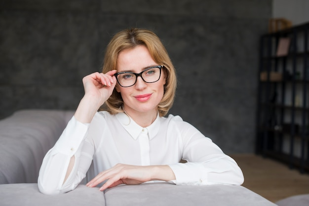 Blond business woman in glasses sitting on couch