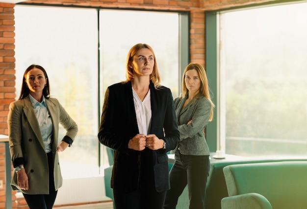 新しいオフィスの金髪のビジネスウーマン、2人の同僚。現代のオフィスのインテリアで若いビジネス女性の肖像画。チームワークの概念。