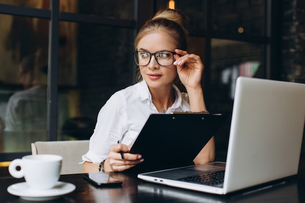Blond business woman sitting on workspace and using laptop at office, she looks at a folder with documents, talking by phone and drinking cup of coffee.