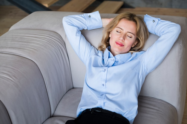 Blond business woman sleeping on couch