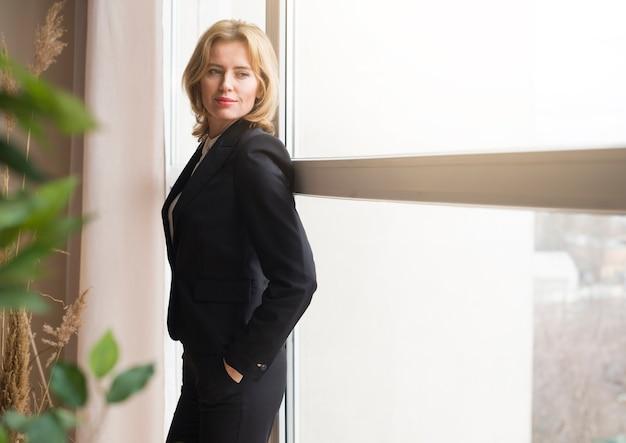 Donna bionda di affari che si leva in piedi alla finestra