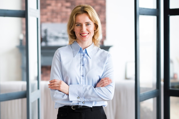 Blond business woman standing with crossed arms