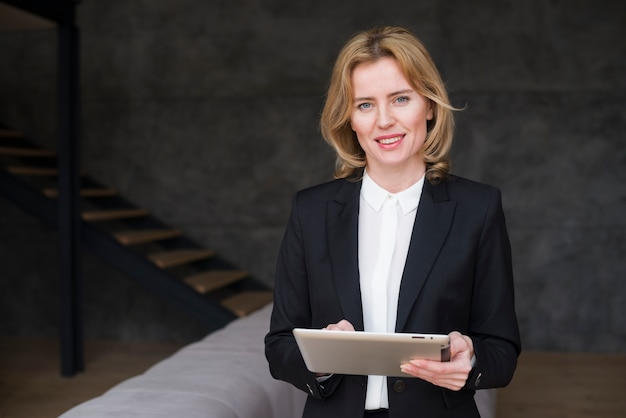 Blond business woman in suit using tablet